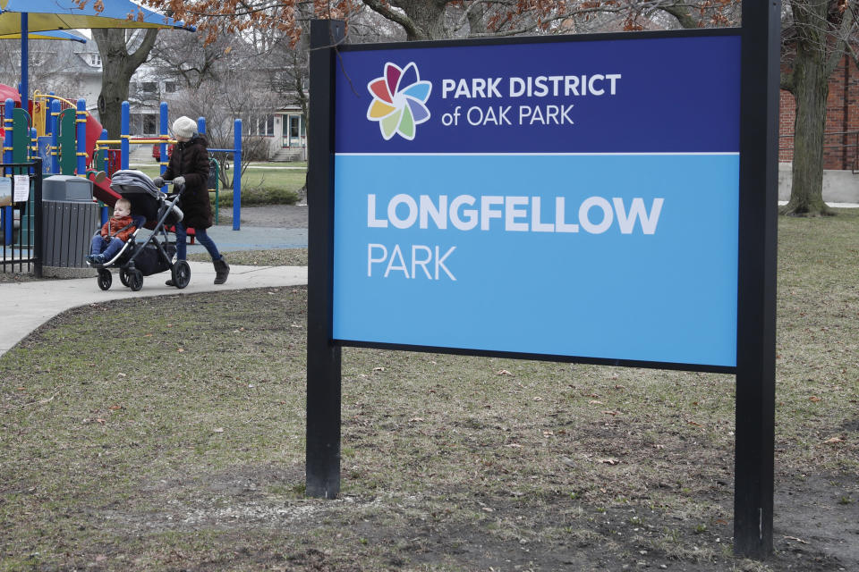 A resident of the Village of Oak Park, Ill., walks with a child in Longfellow Park, Friday, March 20, 2020. There are at least three confirmed cases of COVID-19 in Oak Park, just nine miles from downtown Chicago, where the mayor has ordered residents to shelter in place. With so few tests available, surely there are others, says Tom Powers, spokesman for the village of about 52,000 in a metropolitan area with millions. (AP Photo/Charles Rex Arbogast)
