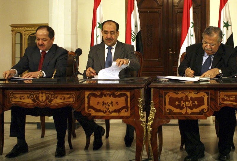FILE- In this Aug. 16, 2007 file photo, Iraqi Prime Minister Nouri al-Maliki, center, and President Jalal Talabani, right, and leader of the northern autonomous Kurdish region, Massoud Barzani, left, as they sign a three-page agreement on a new alliance of moderate Shiites and Kurds at a meeting in Baghdad, Iraq. (AP Photo/ Khalid Mohammed, File)