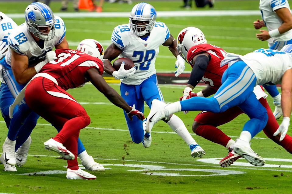 Lions running back Adrian Peterson looks for an opening as Arizona Cardinals free safety Chris Banjo defends during the first half on Sunday, Sept. 27, 2020, in Glendale, Ariz.