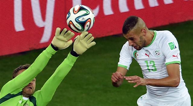 Algeria's forward Islam Slimani (R) heads the ball to score a goal past Russia's goalkeeper Igor Akinfeev during a World Cup match in Curitiba on June 26, 2014 (AFP Photo/Pedro Ugarte)