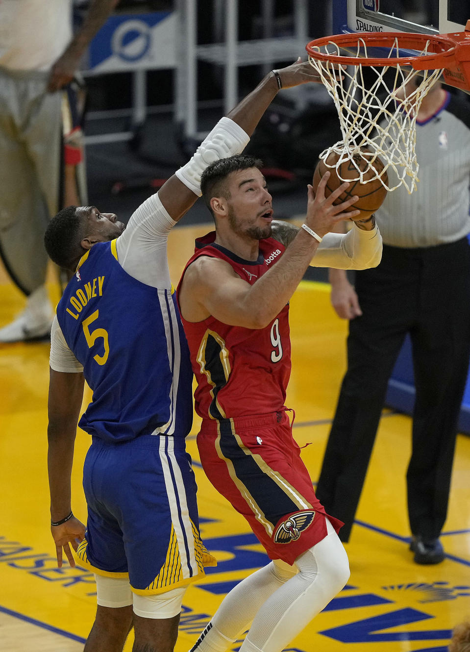 New Orleans Pelicans center Willy Hernangomez (9) drives to the basket against Golden State Warriors center Kevon Looney (5) during the first half of an NBA basketball game on Friday, May 14, 2021, in San Francisco. (AP Photo/Tony Avelar)