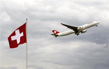 An Airbus A 330-343E of Swiss airlines takes-off past a Swiss national flag from the airport in Zurich