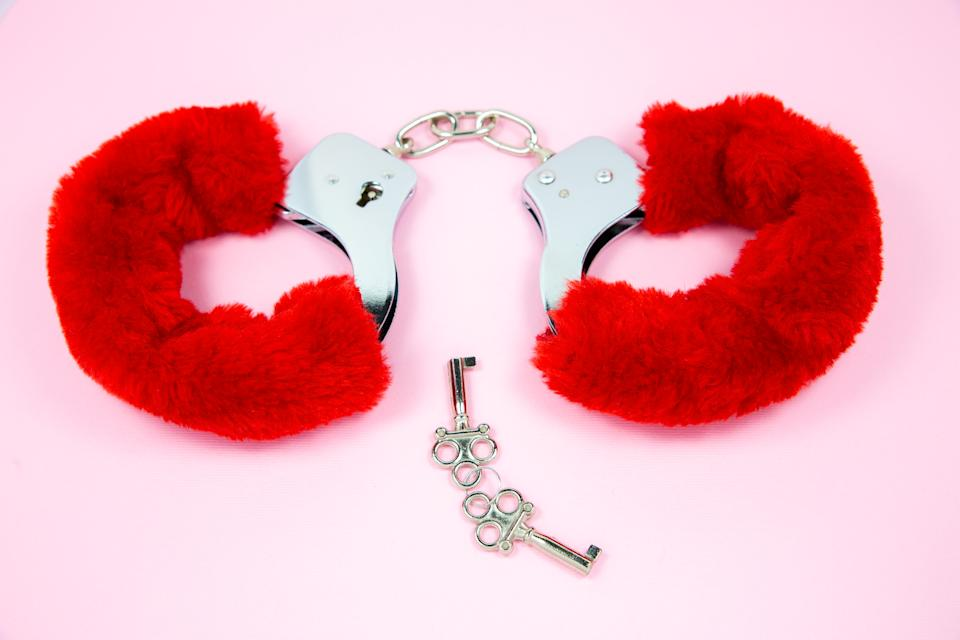 Red sexy fluffy handcuffs with keys on a pink background.