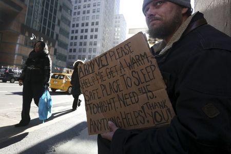 A homeless man sits with a sign on Lexington Avenue in the Manhattan borough of New York, January 4, 2016.REUTERS/Carlo Allegri