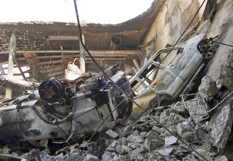 Vehicles that plunged down during the collapse of the upper car park level lie amidst the rubble below, viewed from the basement car park, at the Westgate Mall in Nairobi, Kenya Saturday, Sept. 28, 2013. Kenya's military caused the collapse of three floors of the Westgate Mall in the deadly terrorist siege, a top-ranking official has disclosed, while the government urged patience with the pace of an investigation that has left key questions unanswered. (AP Photo/Ben Curtis)