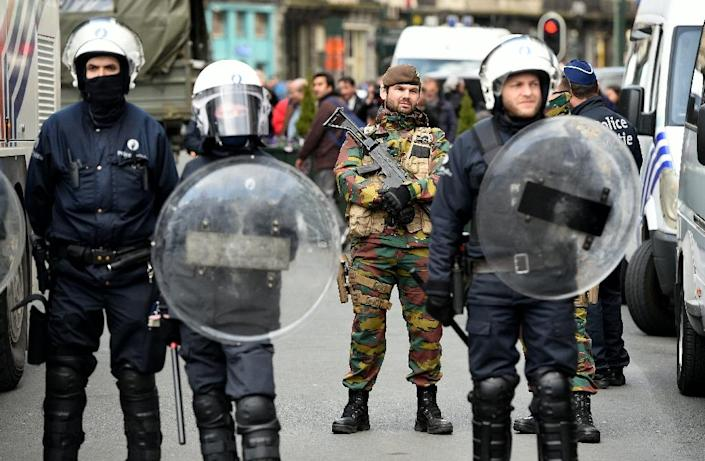 Riot police and soldiers stand guard at Place de la Bourse in Brussels on March 27, 2016 (AFP Photo/Patrik Stollarz)
