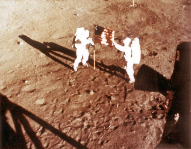 """NASA photo taken on July 20, 1969 shows US astronauts Neil Armstrong and """"Buzz"""" Aldrin deploying the US flag on the lunar surface during the Apollo 11 mission"""