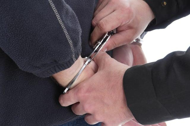 Closeup of policeman's hands handcuffing man