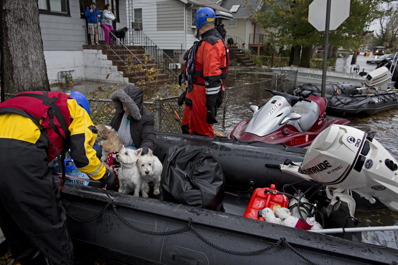 Esperanza Medina, second from left, is taken from a rescue boat along with pets in Little Ferry, N.J., Tuesday, Oct. 30, 2012, in the wake of superstorm Sandy as hundreds were brought out of flooded areas by boat. (AP Photo/Craig Ruttle)