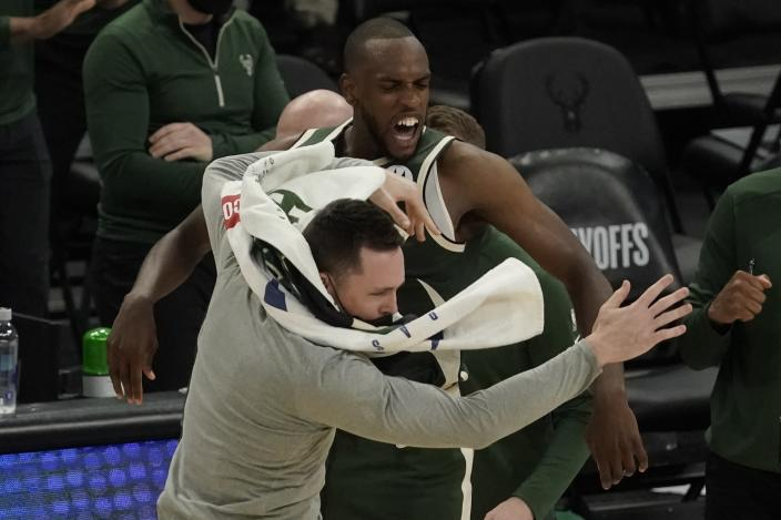 Milwaukee Bucks' Khris Middleton celebrates with teammate Pat Connaughton after making a basket in the final seconds of overtime of Game 1 of their NBA basketball first-round playoff series against the Miami Heat Saturday, May 22, 2021, in Milwaukee. The Bucks won 109-107 to take a 1-0 lead in the series. (AP Photo/Morry Gash)