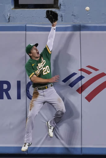 Oakland Athletics center fielder Mark Canha can't make the catch on a home run by Los Angeles Dodgers' A.J. Pollock during the fourth inning of a baseball game Tuesday, Sept. 22, 2020, in Los Angeles. (AP Photo/Ashley Landis)