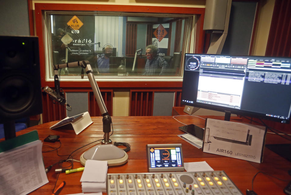 Klubradio's director and CEO Andras Arato, right, and his colleague Milhaly Hardy are seen behind a soundproof window in the studio of Klubradio in Budapest, Tuesday, Feb. 9, 2021. One of Hungary's last remaining independent radio stations will be forced off the airwaves and limited to online broadcasts after a court upheld a decision by media regulators not to extend its broadcasting license. The court dismissed a challenge brought by Klubradio, a liberal-leaning commercial station broadcasting in Budapest. (AP Photo/Laszlo Balogh)