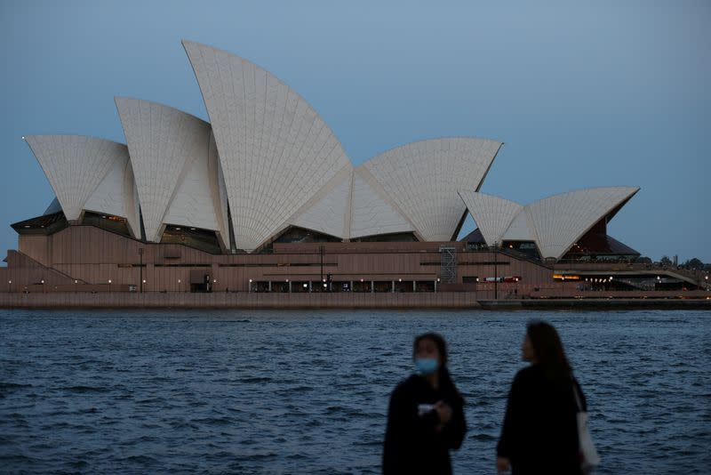FILE PHOTO: People stand on the harbour waterfront near the Sydney Opera House in Sydney