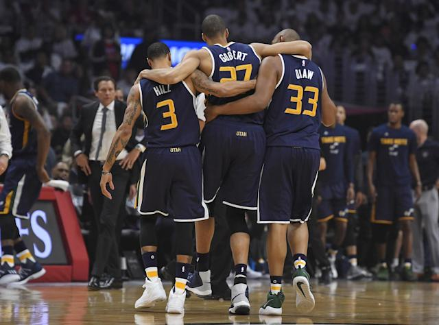 Jazz center Rudy Gobert, center, is helped off the court by center Boris Diaw, right, and guard George Hill, left, on Saturday. (AP)