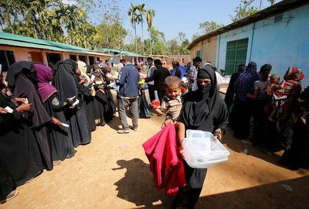A Rohingya refugee woman walks out with a blanket and containers, distributed by the Bangladesh Red Crescent Society, at Kutupalang Unregistered Refugee Camp in Cox's Bazar