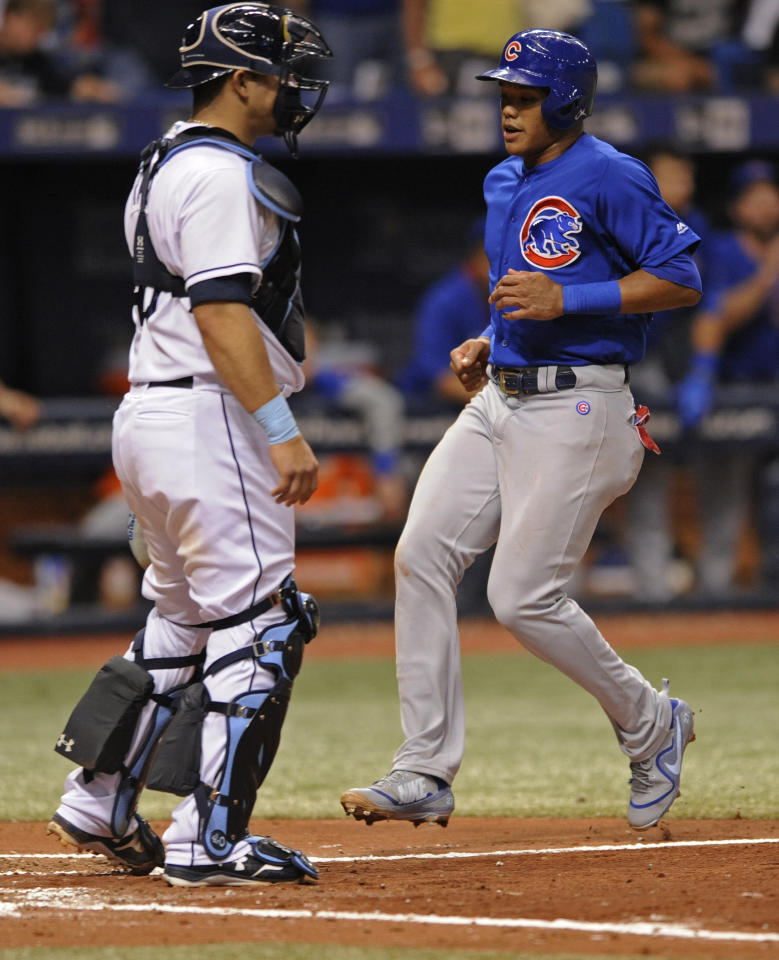 Tampa Bay Rays catcher Wilson Ramos, left, looks on as Chicago Cubs' Addison Russell scores on a RBI-double by Javier Baez during the fourth inning of a baseball game Tuesday, Sept. 19, 2017, in St. Petersburg, Fla. (AP Photo/Steve Nesius)