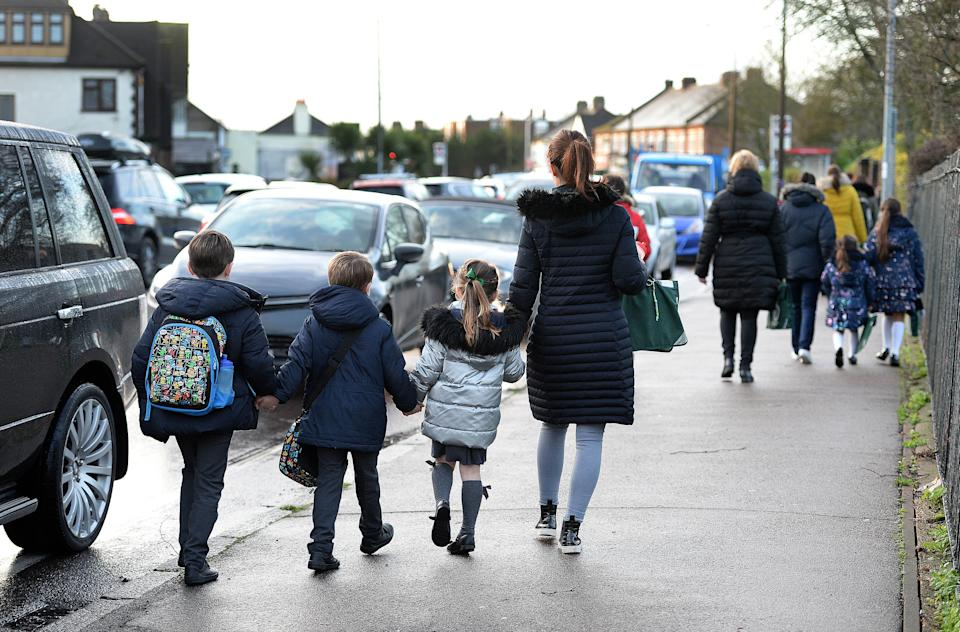 Parents walk their children to school in Hornchurch, Essex, past stationary vehicles near to the school grounds. PA Photo. Picture date: Friday January 17, 2020. Photo credit should read: Nick Ansell/PA Wire (Photo by Nick Ansell/PA Images via Getty Images)