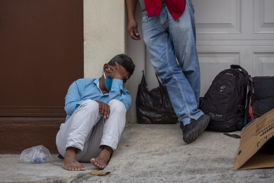 A homeless man, wearing mask against the spread of the new coronavirus, waits to enter to a temporary shelter before the stay-at-home curfew in Guatemala City, Wednesday, April 1, 2020. For most people, the new coronavirus causes mild or moderate symptoms, such as fever and cough that clear up in two to three weeks. (AP Photo/Moises Castillo)