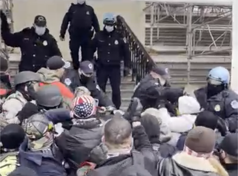 In a still from video released Monday, Charles Donohoe can be seen standing amid a mob of rioters facing off against police guarding scaffolding outside the Capitol building. / Credit: Government exhibit