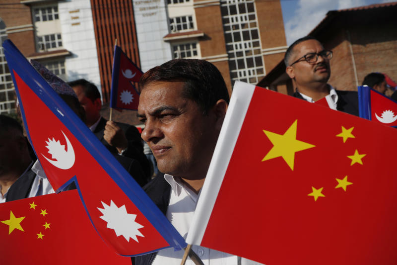 A Nepalese man holds Chinese and Nepalese flag as he waits to welcome Chinese president Xi Jinping in Kathmandu, Nepal, Saturday, Oct 12, 2019. Xi arrived Saturday from New Delhi, where he met with Indian Prime Minister Narendra Modi. He was received by Nepalese President Bidhya Devi Bhandari and Prime Minister K.P. Sharma Oli at the Kathmandu airport. (AP Photo/Niranjan Shrestha)