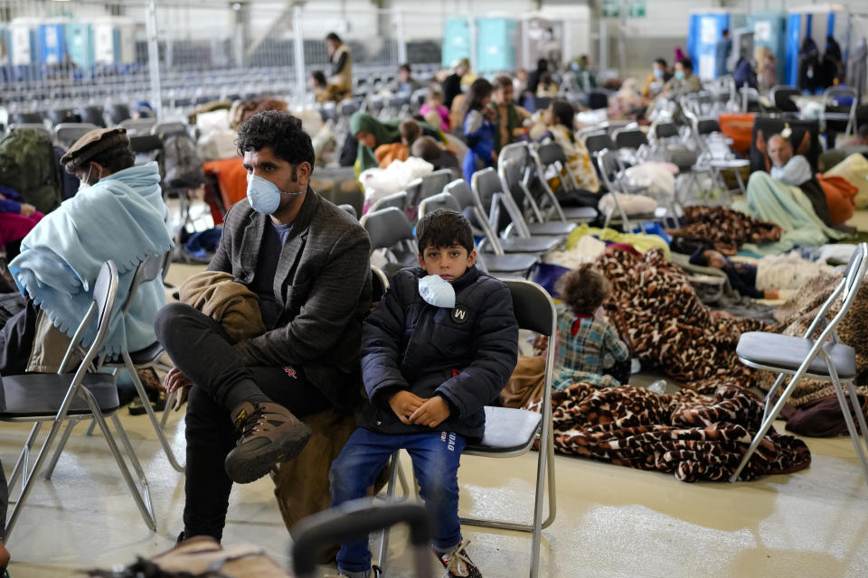 Evacuees from Afghanistan wait with other evacuees to fly to the United States or an other save location in a makeshift departure gate inside a hanger at the United States Air Base in Ramstein, Germany, Wednesday, Sept. 1, 2021. One of largest American military community overseas gets to a transport hub and houses thousands Afghan evacuees. (AP Photo/Markus Schreiber
