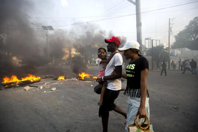 <p>People walk past a barricade during a protest over the cost of fuel in Port-au-Prince, Haiti, Friday, July 6, 2018. (Photo: Dieu Nalio Chery/AP) </p>