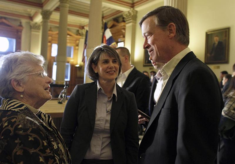 """This photo taken Jan. 3, 2013 shows Colorado Gov. John Hickenlooper, right, with Sue Birch, Executive Director of the Colorado Department of Health Care Policy and Financing, center, speaking with an attendee of a news conference where Hickenlooper announced a plan to expand Medicaid coverage for adults as called for by President Barack Obama's federal health care law, at the state Capitol in Denver. The underdog of government health care programs is emerging as the rare early success story of President Barack Obama's technologically challenged health overhaul. A yearslong effort to reach eligible residents apparently succeeded in generating the increased demand. The state has installed self-service kiosks in community clinics, hospitals and libraries to sign people up. And a year ago, nurses statewide agreed to help by promoting Medicaid to low-income uninsured patients. """"We said to our nurses: 'OK, you're our bounty hunters. You go find our patients,'"""" Birch said. (AP Photo/Brennan Linsley)"""