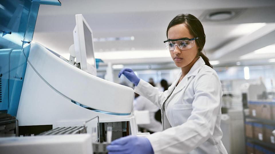 Shot of a young woman using a machine to conduct a medical test in a laboratory.