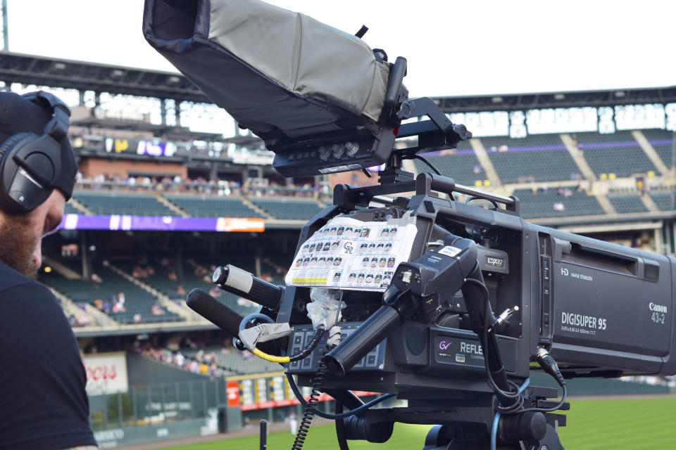DENVER, COLORADO - AUGUST 31, 2019: A television cameraman prepares to operate a TV camera during a live broadcast of a Colorado Rockies Major League Baseball game at Coors Field in Denver, Colorado. (Photo by Robert Alexander/Getty Images)