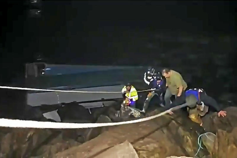 This photo from video provided by Rob Gensorek of Basin Tackle Charleston shows firefighters rescuing the crew from a capsized crab boat in the harbor at Coos Bay, Ore., late Tuesday evening, Jan. 14, 2020. Three men were in good condition early Wednesday after being cut from inside the hull of the capsized boat. The 38-foot (11-meter) Pacific Miner was flipped upside-down by large waves late Tuesday and then got caught on rocks in a jetty in Coos Bay as the tide went out. A U.S. Coast Guard helicopter on a routine training mission spotted the vessel and launched a rescue, the agency said in a news release. (Rob Gensorek of Basin Tackle Charleston via AP)