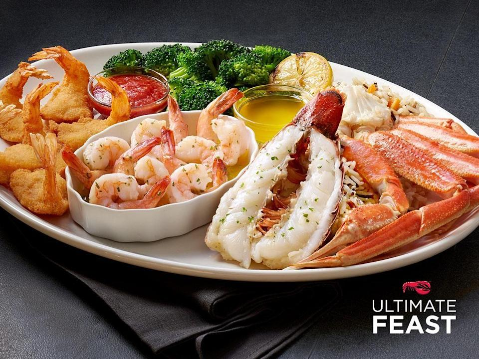 """<p>The only tough part of eating at a crowd-pleasing restaurant like Red Lobster is deciding what to order, and <a href=""""https://www.redlobster.com/menu/shrimp-lobster-crab-combinations/ultimate-feastr"""" rel=""""nofollow noopener"""" target=""""_blank"""" data-ylk=""""slk:The Ultimate Feast"""" class=""""link rapid-noclick-resp"""">The Ultimate Feast</a> removes all the pressure. Have your lobster and eat it, too! And your snow crab legs...and your garlic shrimp scampi...and your """"Walter's Favorite Shrimp""""...<em>and</em> your rice and choice of side. The only, er, """"<a href=""""https://www.delish.com/food-news/a22767295/red-lobster-ultimate-feast-price-increase/"""" rel=""""nofollow noopener"""" target=""""_blank"""" data-ylk=""""slk:controversy"""" class=""""link rapid-noclick-resp"""">controversy</a>"""" about The Ultimate Feast might be the fact that it costs $30.</p>"""