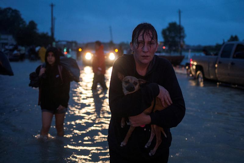 A woman holds her dog on Monday as she arrives to high ground after evacuating her home in east Houston. (Adrees Latif / Reuters)