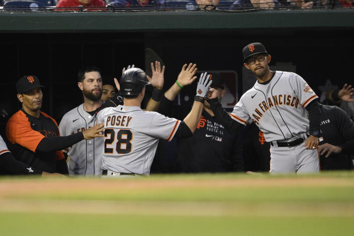 San Francisco Giants' Buster Posey (28) is congratulated in the dugout after his home run during the fourth inning of a baseball game against the Washington Nationals, Friday, June 11, 2021, in Washington. (AP Photo/Nick Wass)