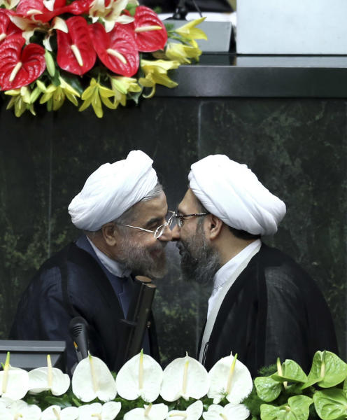 "Iran's new President Hasan Rouhani, left, and judiciary chief Sadeq Larijani, greet each other after Rouhani swore-in at the parliament, in Tehran, Iran, Sunday, Aug. 4, 2013. Iran's new president on Sunday called on the West to abandon the ""language of sanctions"" in dealing with his country over its contentious nuclear program, hoping to ease the economic pressures now grinding its people. Rouhani spoke after being sworn in as president in an open session of parliament Sunday, capping a weekend that saw him endorsed by Ayatollah Ali Khamenei, Iran's supreme leader. Parliament speaker Ali Larijani, sits top center. (AP Photo/Ebrahim Noroozi)"