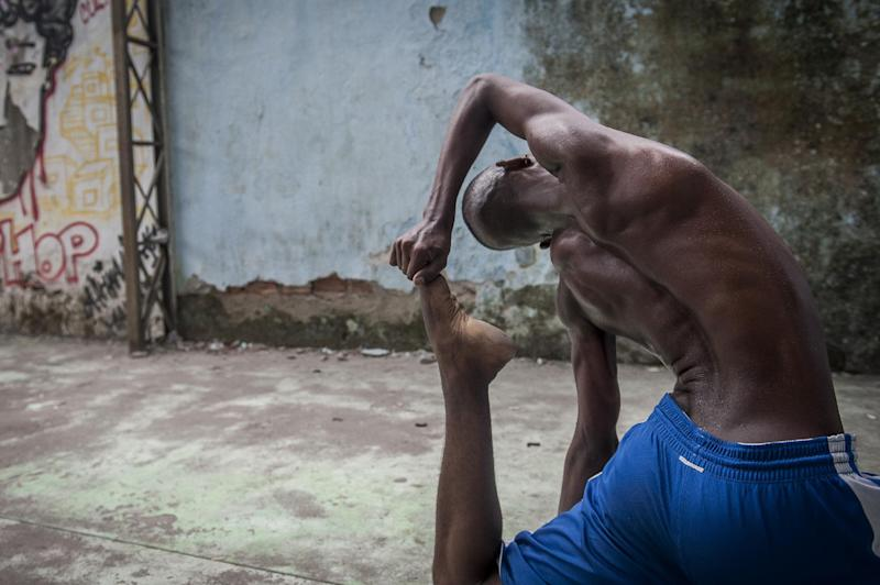"""In this Aug. 17, 2013 photo, Hilton Santos da Cruz Jr. practices during a """"passinho,"""" or """"little step,"""" session at a makeshift dance studio in the Borel favela, Rio de Janeiro, Brazil. The dance's popularity has benefited from a police crackdown on another late night activity, more raucous """"baile funk"""" parties often organized by criminal gangs. In passinho gatherings, participants watch as performers square off against each other in choreographed duels. The dance's new superstars include Cruz, known as """"Hiltinho Fantastico"""" or Fantastic Little Hilton. (AP Photo/Nicolas Tanner)"""
