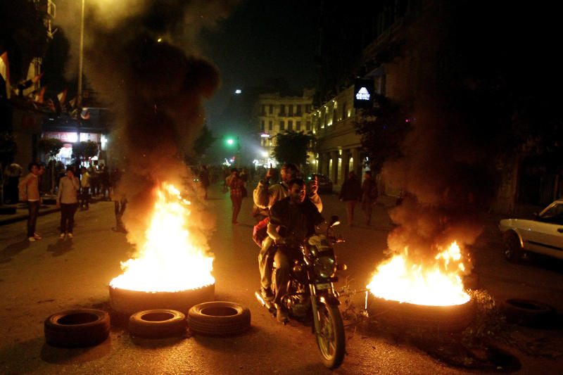 In this Tuesday, Nov. 26, 2013 photo, a motorcycle passes burning tires during a protest in Talaat Harb Square in Downtown, Cairo, Egypt. Egypt's state news agency says the prosecutor general has ordered a four-day detention for 24 activists detained while protesting a newly passed law criminalizing demonstrations without permits. MENA also says the prosecutor on Wednesday issued arrest warrants for two leading activists accused of inciting demonstrators. (AP Photo/El-Shorouk Newspaper, Ahmed Abd el-Latif) EGYPT OUT