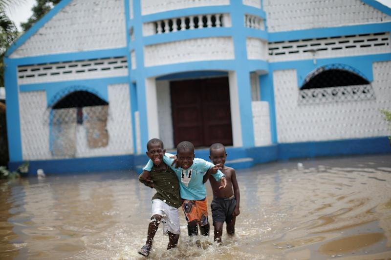 Boys walk in a flooded area in Fort Liberte, Haiti