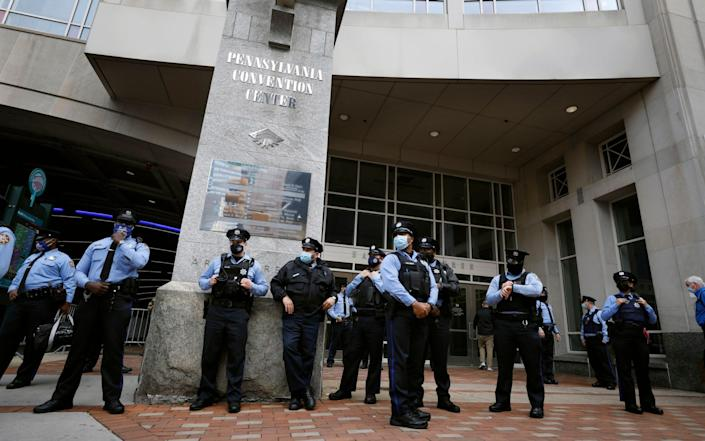 Police officers stand outside the Pennsylvania Convention Center  - AP