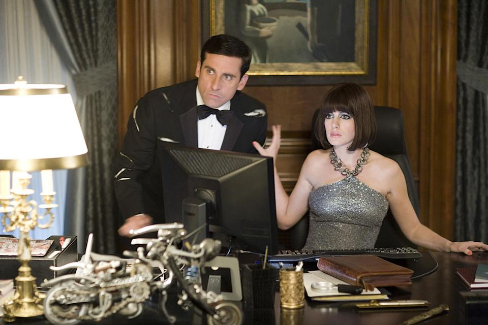 Steve Carell and Anne Hathaway dressed up while on the computer looking startled and serious