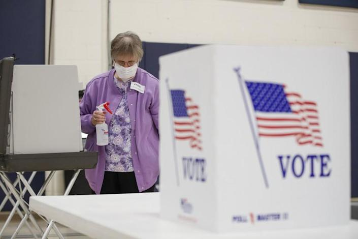 """An election observer cleans voting booths during the Democratic presidential primary election in Kenosha, Wis., on April 7. <span class=""""copyright"""">(AFP / Getty Images)</span>"""