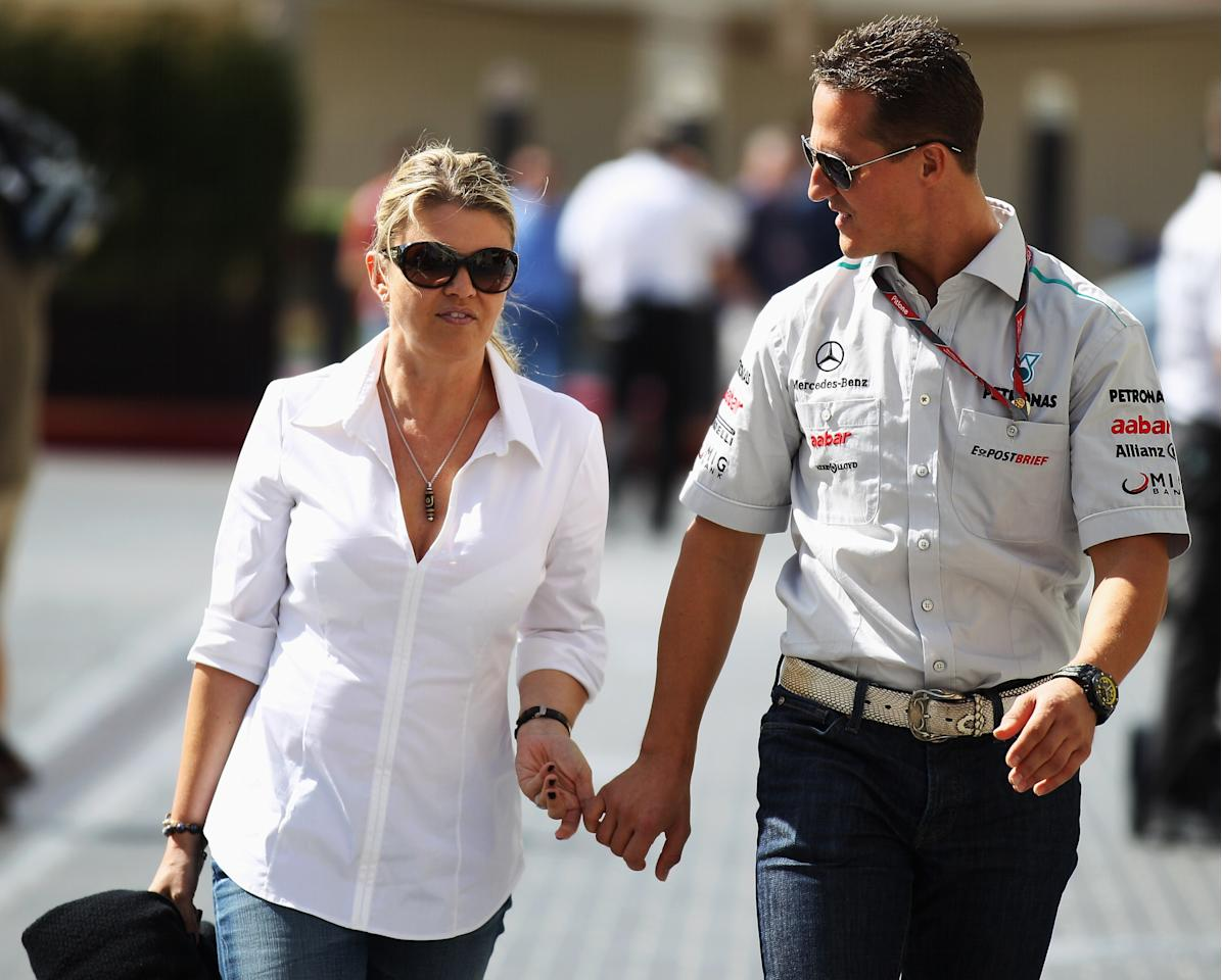 ABU DHABI, UNITED ARAB EMIRATES - NOVEMBER 10:  Michael Schumacher of Germany and Mercedes GP walks with his wife Corrina in the paddock during previews to the Abu Dhabi Formula One Grand Prix at the Yas Marina Circuit on November 10, 2011 in Abu Dhabi, United Arab Emirates.  (Photo by Mark Thompson/Getty Images)