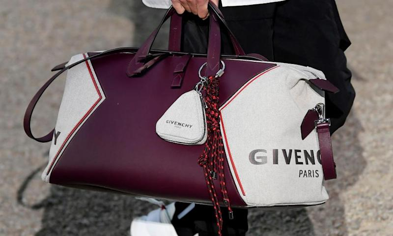 A branded Givenchy bag is carried by a model