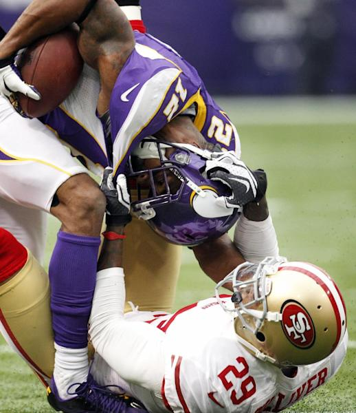 Minnesota Vikings wide receiver Percy Harvin, top, is tackled by San Francisco 49ers defensive back Chris Culliver after making a reception during the first half of an NFL football game on Sunday, Sept. 23, 2012, in Minneapolis. (AP Photo/Genevieve Ross)