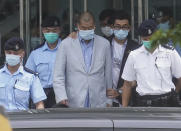 Hong Kong media tycoon Jimmy Lai, center, who founded the local newspaper Apple Daily, is escorted by police from the leave the Apple Daily headquarters in Hong Kong, Monday, Aug. 10, 2020. Lai was arrested Monday on suspicion of collusion with foreign powers, his aide said, in the highest-profile use yet of the new national security law Beijing imposed on the city after protests last year. (AP Photo)