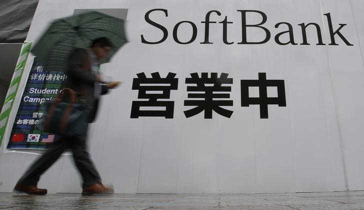 A man holding an umbrella walks past the logo of Softbank Corp at its branch in Tokyo
