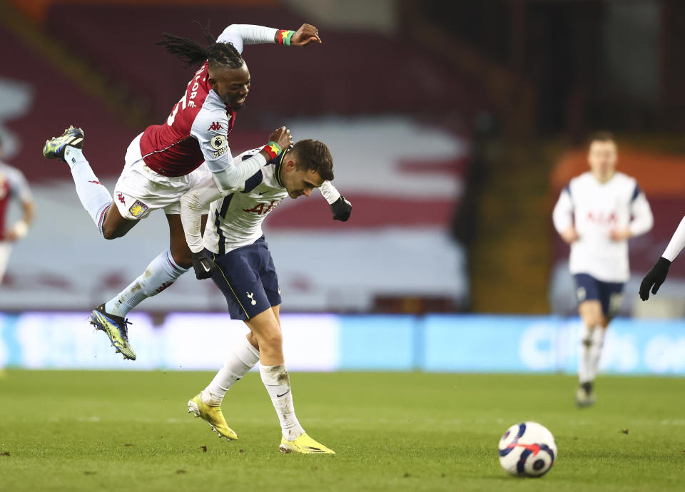 Aston Villa's Bertrand Traore, left, is airborne as he tangles with Tottenham's Sergio Reguilon during the English Premier League soccer match between Aston Villa and Tottenham Hotspur at Villa Park in Birmingham, England, Sunday, March 21, 2021. (AP Photo/Michael Steele,Pool)