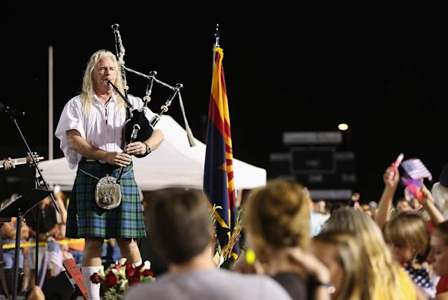 "PRESCOTT, AZ - JULY 02: A bagpiper plays ""Amazing Grace"" at the candlelight vigil in honor of the 19 fallen firefighters at Prescott High School on July 2, 2013 in Prescott, Arizona. 19 Granite Mountain Interagency Hotshot Crew firefighters died battling a fast-moving wildfire near Yarnell, AZ on Sunday. (Photo by Christian Petersen/Getty Images)"