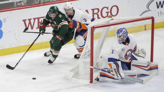 Minnesota Wild left wing Zach Parise (11) battle New York Islanders defenseman Adam Pelech (3) behind the net as Islanders goaltender Thomas Greiss (1), of Germany, looks on during the first period of an NHL hockey game Sunday, March 17, 2019, in St. Paul, Minn. (AP Photo/Paul Battaglia)