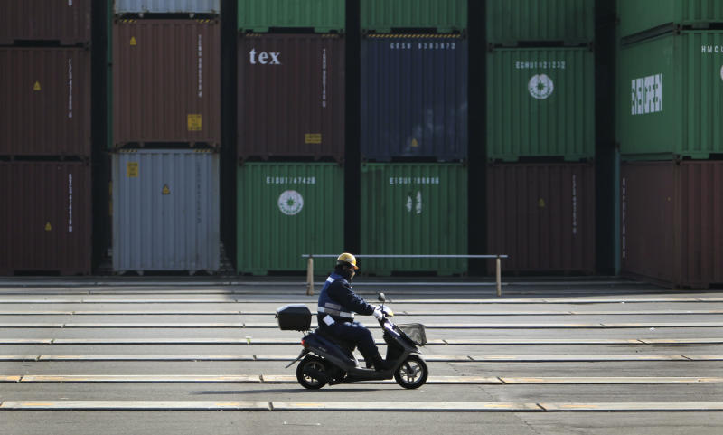 FILE- In this Wednesday, Jan. 25, 2012, file photo, a worker rides a motorbike at a container terminal in Tokyo. The U.S. current account trade deficit widened in the first three months to the largest imbalance since late 2008, reflecting a big increase in imports in oil, cars and machinery and a drop in U.S. earnings on overseas investments.(AP Photo/Junji Kurokawa, File)