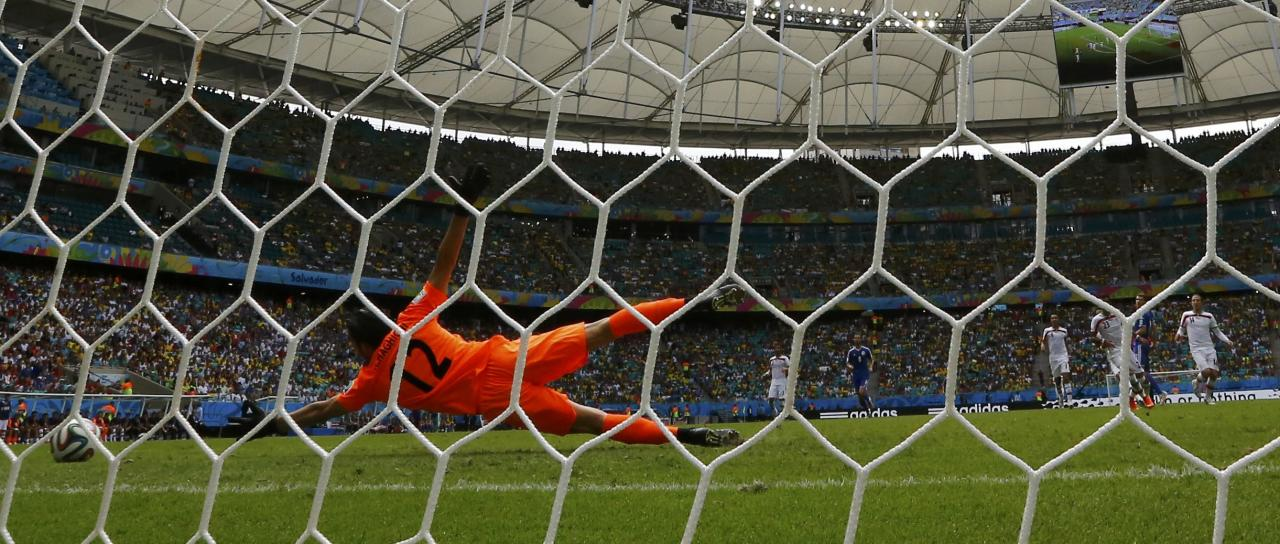Iran's goalkeeper Alireza Haghighi (L) fails to save a goal by Bosnia's Edin Dzeko during their 2014 World Cup Group F soccer match at the Fonte Nova arena in Salvador June 25, 2014. REUTERS/Marcos Brindicci (BRAZIL - Tags: SOCCER SPORT WORLD CUP)